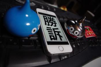 勝訴と表示されているiPhoneの両隣にスライムがいる画像