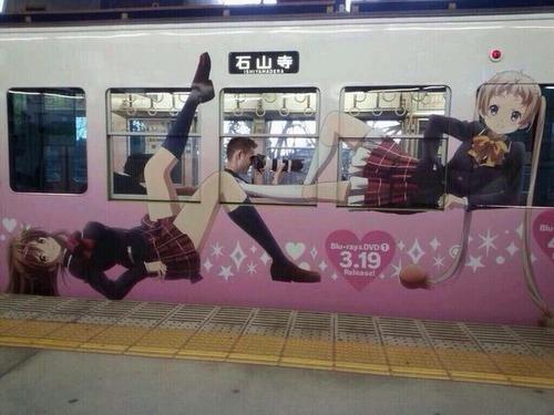 電車に描かれたアニメ美少女のスカートの中を撮影する男性の写真