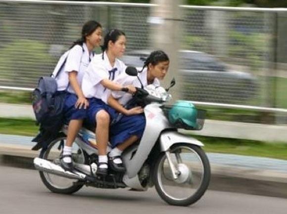 タイの女子高生がバイクに3人乗りしている写真